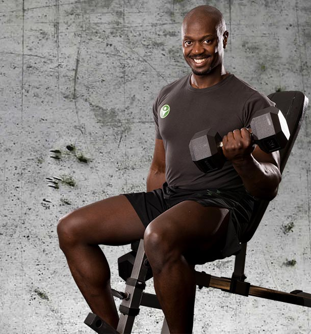 Hakim Isler seated on gym equipment with dumbbell