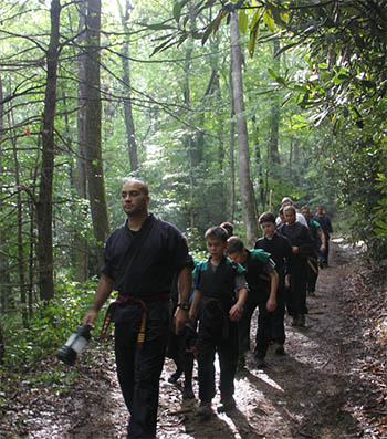 Group of Elevo Dynamics students being led along a path in the woods